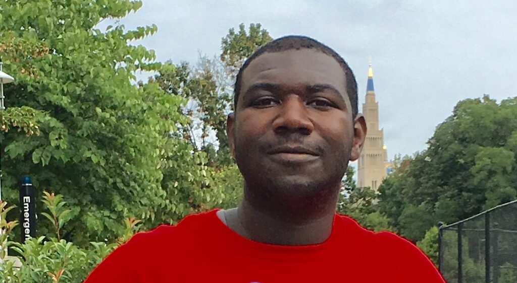Photo of Deion, a young African American man with short hair and the faint traces of a beard and mustache, smiles with trees and the National Cathedral in the background behind him. He is wearing a red shirt.