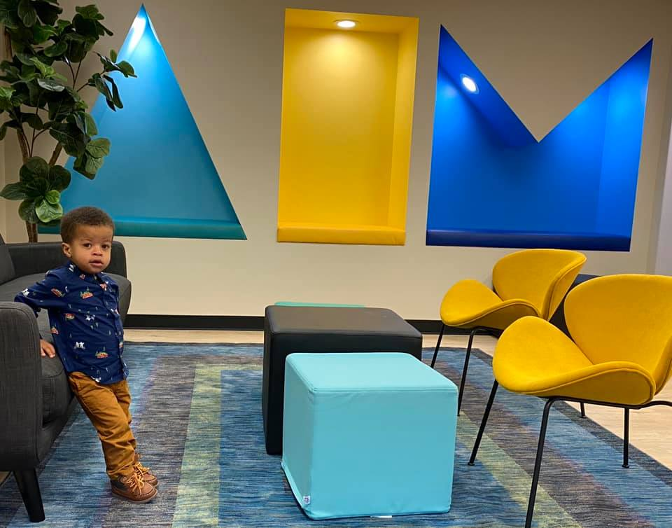 Photo of young African American child with short hair, wearing a dark collared shirt with little designs on it and khaki pants. Greyson is leaning against a couch in a lobby with furniture and wall decorations in teal and grey.