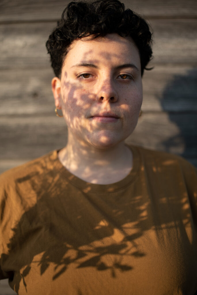 Photo of Heather, a young latinx & mestizo, (afroperuvian, indigenous, and white) woman with short dark curly hair combed upward, looks directly at the camera against a wooden wall. She is wearing a red shirt and small gold earrings.