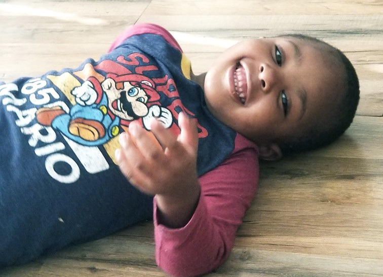 Photo of Jahmai, a young Black child with short hair, lies on a wooden floor and smiles at the camera, gesturing outward with one hand. Jahmai is wearing a Super Mario t-shirt.