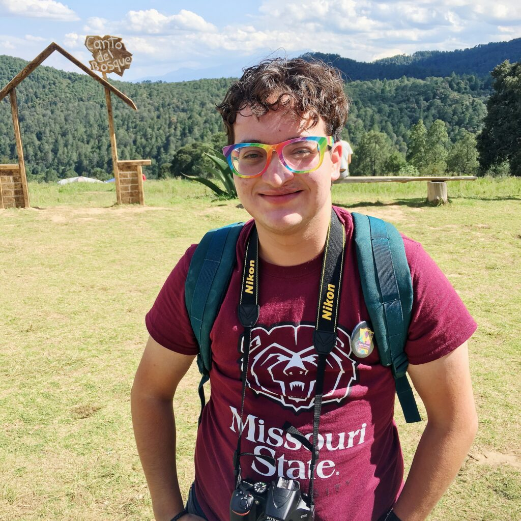 Photo of Jamie, a young Latino man with short curly brown hair and rainbow-framed glasses, smiles while standing in a meadow outdoors. There are forests of evergreen trees behind the meadow, and a wooden sign that says Canto del Bosque behind him. He is wearing a red t-shirt with the Missouri State mascot Boomer the Bear, a backpack, and a camera around his neck.