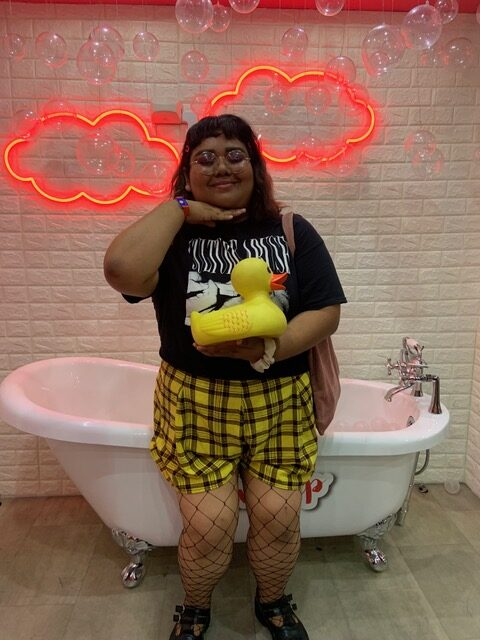 Photo of Jocelyn, a young xicanx person with shoulder length dark wavy hair, poses smiling and eyes closed in front of a free-standing four-claw bathtub, holding one hand below their chil, and holding a large rubber ducky in their other hand. They are wearing glasses, a black t-shirt, plaid shorts, and fishnet tights. There are two pink neon lights in the shape of clouds or bubbles on the wall.