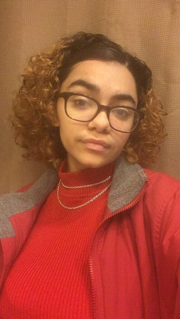 Photo of LaLa, a biracial (Afro-Caribbean and Italian) person with short brown curly hair and glasses, gives a partial smile and tilts their head to the side while looking at the camera. They are wearing glasses, a red jacket, a red sweater, and two small gold chain necklaces.