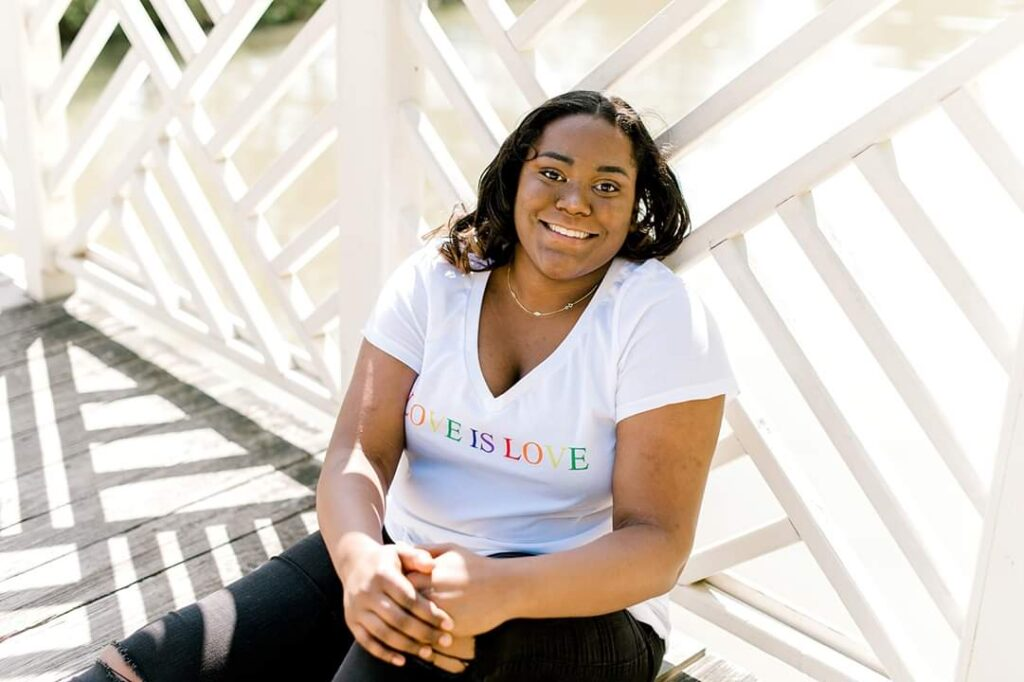 Photo of Lauren, a young African American woman, with shoulder-length straightened hair, smiling while sitting against a white fence on a porch. She is wearing a white t-shirt that says Love Is Love in rainbow letters.