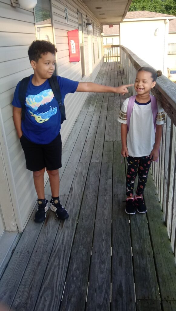 Photo of Mason and Raquel, both biracial children with a Black parent, standing on a wooden porch together. They both grin - Raquel showing recently lost teeth in her smile - and are facing each other, while Mason stretches out his arm to poke his sister. They are both wearing t-shirts, sneakers, and backpacks.