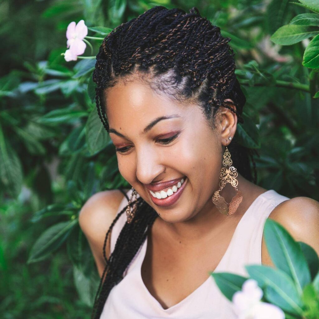 Photo of Naakai, a young Black woman, smiles and looks down and away from the camera while resting amidst leaves and flowers. She wears thin braids, swirling gold dangling earrings, and a white tank top.