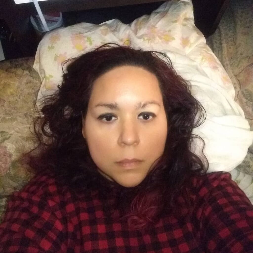 Photo of Noemi, a young Boricua/Chicanx person with shoulder-length dark wavy/curly hair, lies on their back, looking directly at the camera with a serious expression. They are wearing a dark red and black checkered shirt, and have their head on a pillow in a floral design pillowcase.