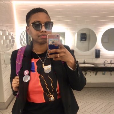 Photo of Xhey, a young Black Indigenous-descended person with short hair, holds their phone in a bathroom to take a selfie. They are wearing sunglasses, and a shirt with a black and pink design, a dark blazer with buttons on it, and holding the strap of a backpack.