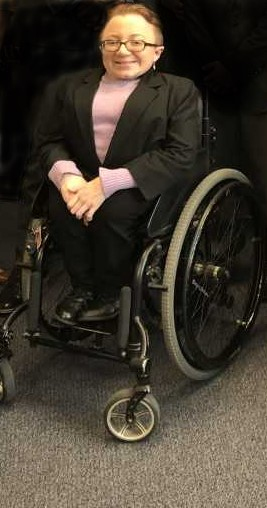 Small, white Hispanic woman sitting in a wheelchair, smiling. She's wearing a black blazer and slacks with a purple sweater and has short, undercut hair and narrow glasses.