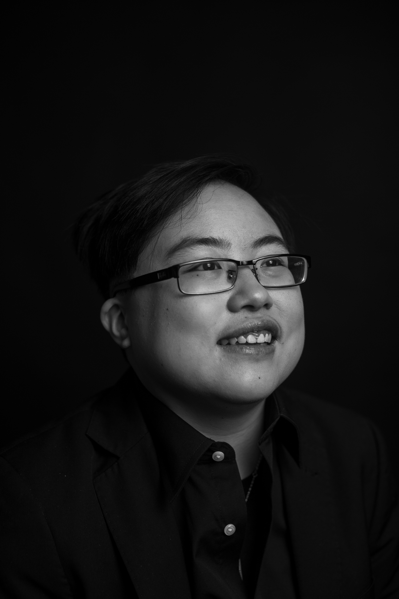 Young East Asian person with short black hair and glasses, smiling and laughing a little as they look to the side. They are wearing all black, and the photo is black and white.