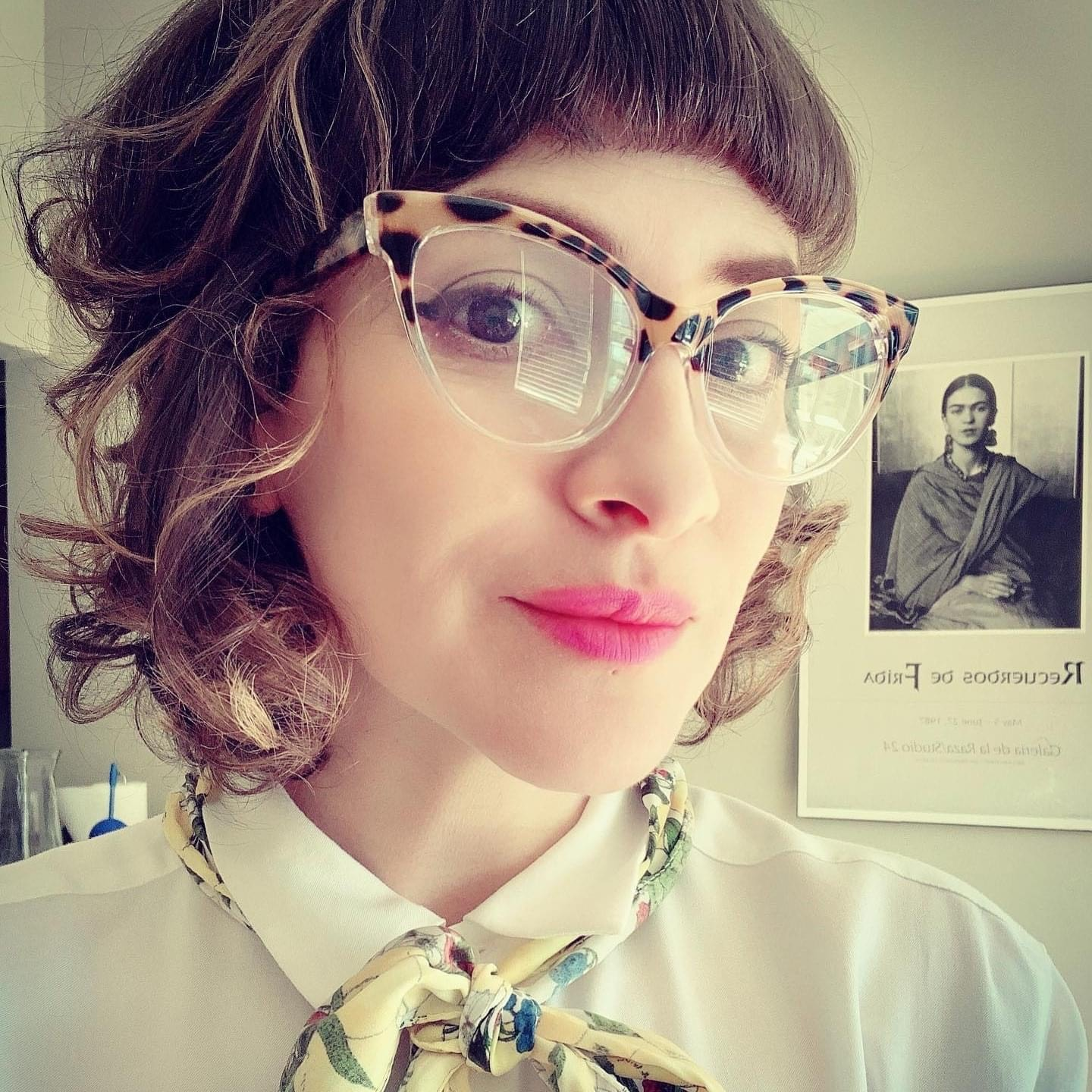 Selfie of a Mestiza woman with curly brown hair just below her chin and bangs and big brown eyes. She wears a collared blouse with a flowered scarf tied at the collar and large cat-eye glasses with cat print frames. She gazes pensively to the camera. Behind her a Frida Kahlo poster showing a portrait of the artist and text in Spanish: Recuerdos de Frida (Frida's Memories)